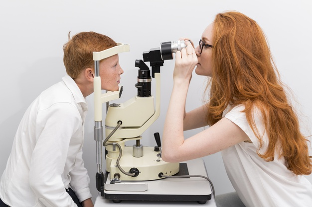 female-eye-doctor-checking-boy-s-eyes-with-refractometer-machine-clinic_23-2148241494